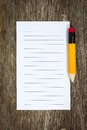 Pencil and lined paper on the wood background Stock Photography