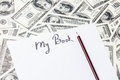 Pencil and paper with my book words one hundred dollar bills Royalty Free Stock Images