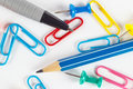 Pencil, pen, paperclip and thumbtack on white desktop closeup Royalty Free Stock Photo
