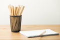 Pencil in pot with notebook on the table Royalty Free Stock Photo