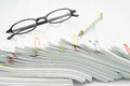Pencil and spectacles place on pile of overload white paperwork reports table Stock Image