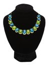 Pendant with green and blue gem stones on black mannequin Royalty Free Stock Photo