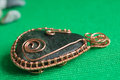 Pendent from the stone braided by a copper wire close up Stock Photo