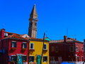 Pending clock tower in burano venice is the colourful village the venetian lagune with its spectacular coloured houses and the Royalty Free Stock Images