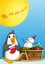 A penguin near the sleigh with a snowman illustration of Stock Photo