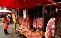 Pengzhou china butcher shop at long xing market with a display of different cuts of pork hanging from iron meat hooks the Stock Photography