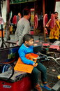 Pengzhou china little boy in bicycle cart a sits a eating finger cookies while his father shops for a cut of fresh pork at the Royalty Free Stock Photography