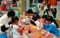 Pengzhou china parents children painting figures and alike having fun white alabaster seated at outdoor tables in Royalty Free Stock Photography