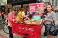 Pengzhou china people buying street food two women selling spicy barbecued meat on skewers from the back of their motorcycle cart Royalty Free Stock Photo