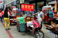 Pengzhou china street vendors selling food woman vendor barbecued meats from the back of her motorcycle cart on a busy shopping in Stock Images