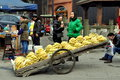 Pengzhou china vendor selling bananas street displayed on a long wooden flatbed cart in Royalty Free Stock Photos