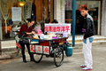 Pengzhou china young man buying food on the street with dyed red hair stops to buy snack from a woman vendor s bicycle cart sheng Royalty Free Stock Photo