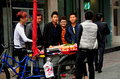 Pengzhou china youths buying apples a group of stop to buy from a street vendor s bicycle cart on sheng shang street in Royalty Free Stock Photography