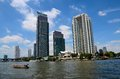 Peninsula Hotel skyscrapers and boat across Chao Phraya River Bangkok Thailand