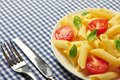 Penne pasta with cherry tomatoes and basil closeup Royalty Free Stock Photo