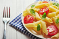 Penne pasta with cherry tomatoes and basil closeup Stock Photo