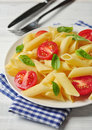 Penne pasta with cherry tomatoes and basil closeup Stock Photography