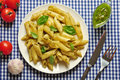 Penne pasta with pesto sauce and basil on white plate Stock Photography