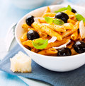 Penne pasta with pesto sauce and olives Stock Photos