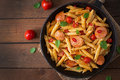 Penne pasta with tomato sauce with sausage, tomatoes, green basil decorated in a frying pan. Royalty Free Stock Photo