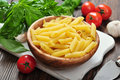 Penne pasta and tomatoes with basil on wooden cutting board Stock Image