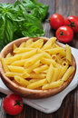 Penne pasta and tomatoes with basil on wooden cutting board Stock Photo