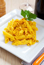Penne with speck and saffron on a dish Stock Images