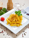 Penne with speck and saffron on a dish Stock Photography