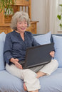 Pensioner with laptop on sofa grey haired laughing in front of her Royalty Free Stock Image
