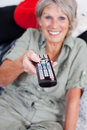 Pensioner with a remote control elderly female lovely smile holding out while changing programs on the television focus to Royalty Free Stock Photo
