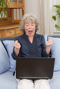 Pensioner screaming at laptop sitting on a sofa her with clenched fists Stock Photos