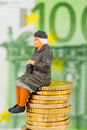 Pensioner sitting on cash pile money stack symbol photo for pension retirement old age security Royalty Free Stock Photography