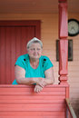 Pensioner thoughtful old woman on the porch of a country house Royalty Free Stock Image