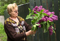Pensioner woman in her country estate with lilac flowers bouquet