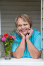 Pensioner woman at window speaking by phone and laughing portrait of Royalty Free Stock Photography