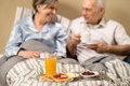 Pensioners drinking coffee in the bed and eating breakfast Royalty Free Stock Photos