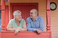Pensioners happy couple on the porch of a country house Stock Photos