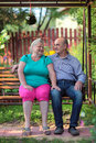 Pensioners happy elderly couple sitting on a bench in a country yard Stock Photography