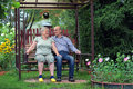 Pensioners happy elderly couple sitting on a bench in a country yard Royalty Free Stock Images
