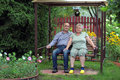 Pensioners happy elderly couple sitting on a bench in a country yard Royalty Free Stock Photos