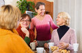 Pensioners having cup of tea happy hot indoor and smiling Royalty Free Stock Photo