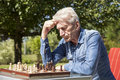 Pensioners playing chess in garden Stock Photo