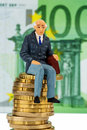 Pensioners sitting on pile of money stack symbol photo for pension retirement old age Stock Photo