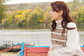 Pensive attractive young woman outdoors sitting in autumn on a rustic wooden bench above a lake or river turned in profile looking Stock Photography