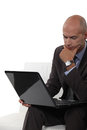 Pensive bald man using laptop Stock Photo
