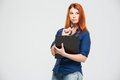 Pensive beautiful redhead young woman holding clipboard and thinking over white background Royalty Free Stock Photography