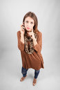 Pensive blue eye beauty talking on the phone looking at camera high angle view wide lens full body length portrait Stock Photo