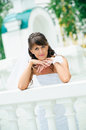 Pensive bride in white dress has leant elbows on handrail Royalty Free Stock Photo
