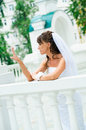 Pensive bride in a white dress looks at manicure Royalty Free Stock Photo