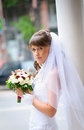 Pensive bride in white dress standing and holding roses bouquet a Stock Photography